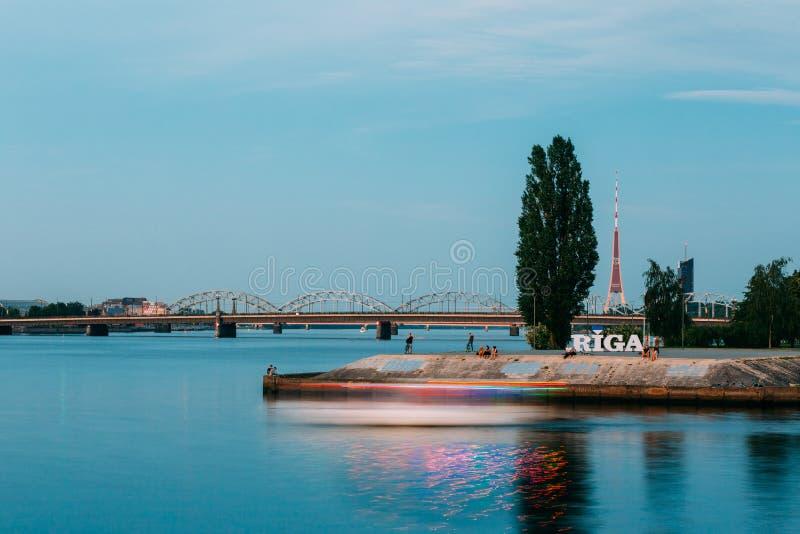 Riga Lettonie Remblai à la rivière de dvina occidentale avec le signe de nom de ville, personnes de repos autour photo stock