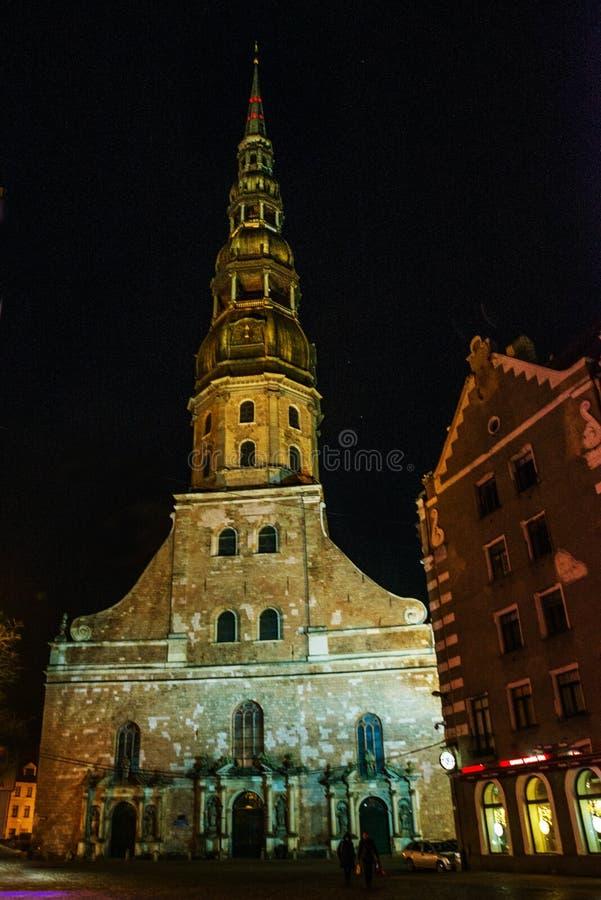 Riga, Lettonie : Vue de nuit de l'église de St Peter dans la vieille ville Riga Lettonie Rue lumineuse photos stock