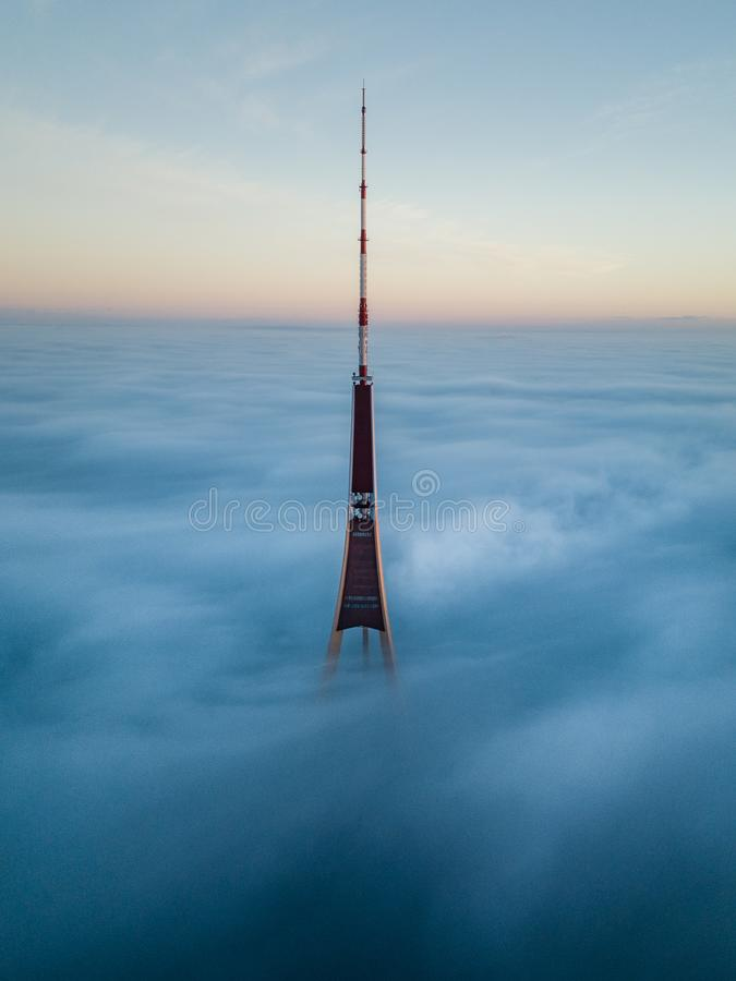 The Riga Radio and TV Tower in Riga, Latvia is the tallest tower in the EU. Tip sticking out of fog layer during sunrise. royalty free stock photos