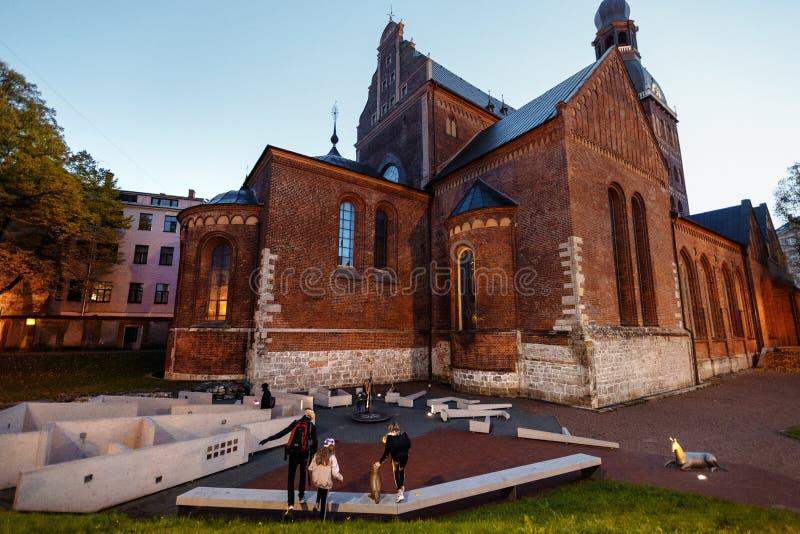 Riga velho na noite, Letónia, Europa - pessoa que anda no ruas históricas da capital europeia - laukums de Doma com imagens de stock royalty free