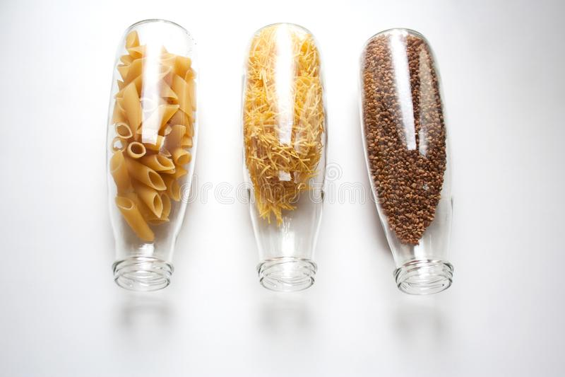 Rigate de Penne, pâtes d'oeufs et sarrasin stockés dans des bouteilles en verre photo libre de droits