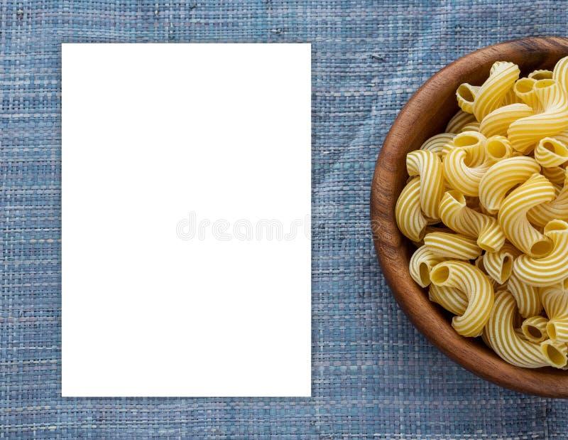 Rigati-Makkaroni in einer hölzernen Schüssel auf einem Blau strickte Hintergrund Leerraum für Text und Ideen lizenzfreies stockbild