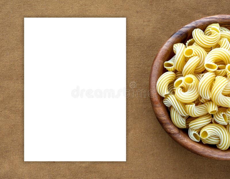Rigati-Teigwaren in der hölzernen Schüssel auf beige braunem Stoffleinwandmuster mit Seite Leerraum für Text und Ideen stockfoto