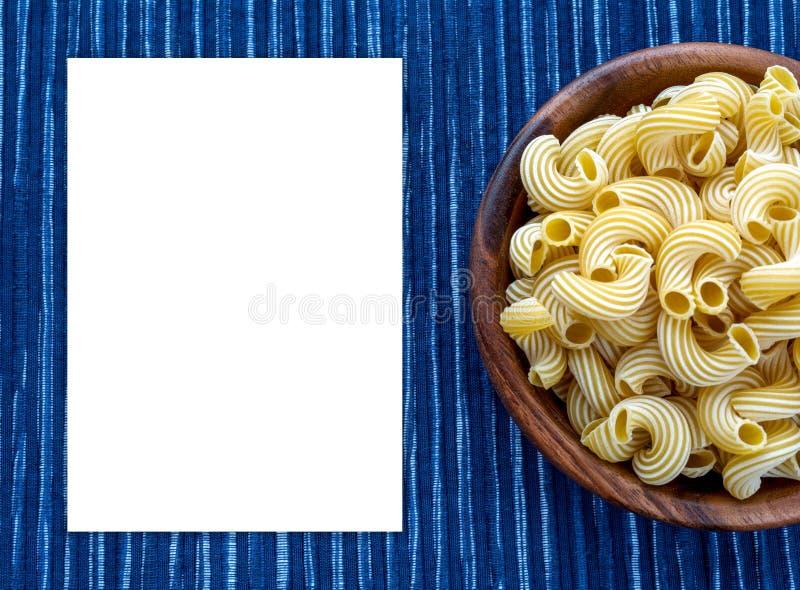 Rigati-Teigwaren in einer hölzernen Schüssel auf einem gestreiften weißen blauen Stoffhintergrund mit einer Seite Leerraum für Te stockbild