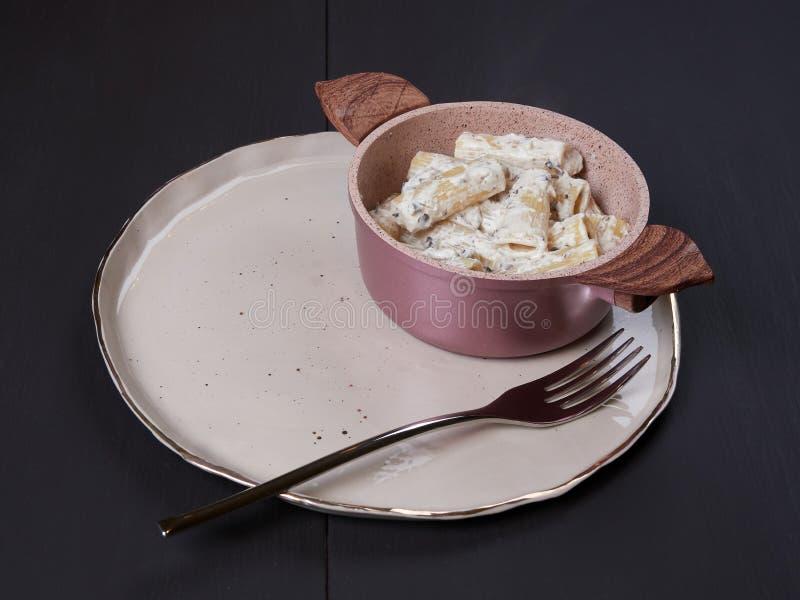 Rigatoni com creme, gorgonzola e azeitonas, em uma placa marrom escura foto de stock
