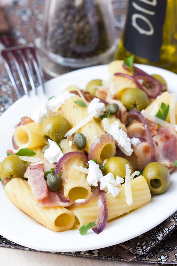 Rigatoni pasta with bacon, green olives, feta cheese, red onion, capers royalty free stock photos