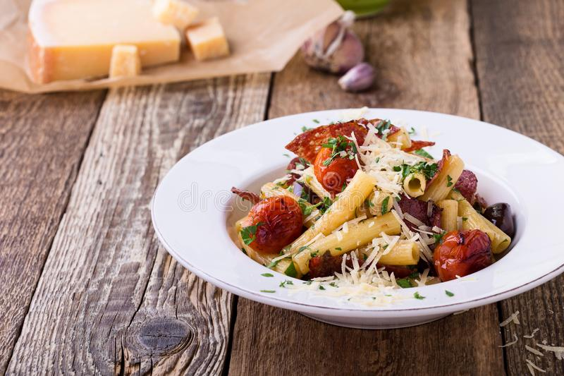 Rigatoni pasta with salami, roasted cherry tomatoes, and olives stock image