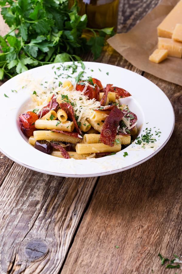 Rigatoni pasta with salami, roasted cherry tomatoes, and olives royalty free stock photo