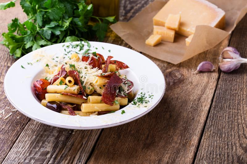 Rigatoni pasta with salami, roasted cherry tomatoes, and olives royalty free stock images