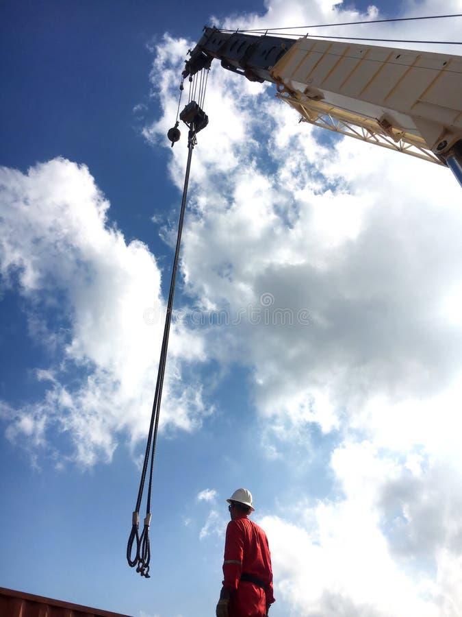 Rigger που λειτουργεί με το γερανό κάτω από το μπλε ουρανό στοκ φωτογραφίες