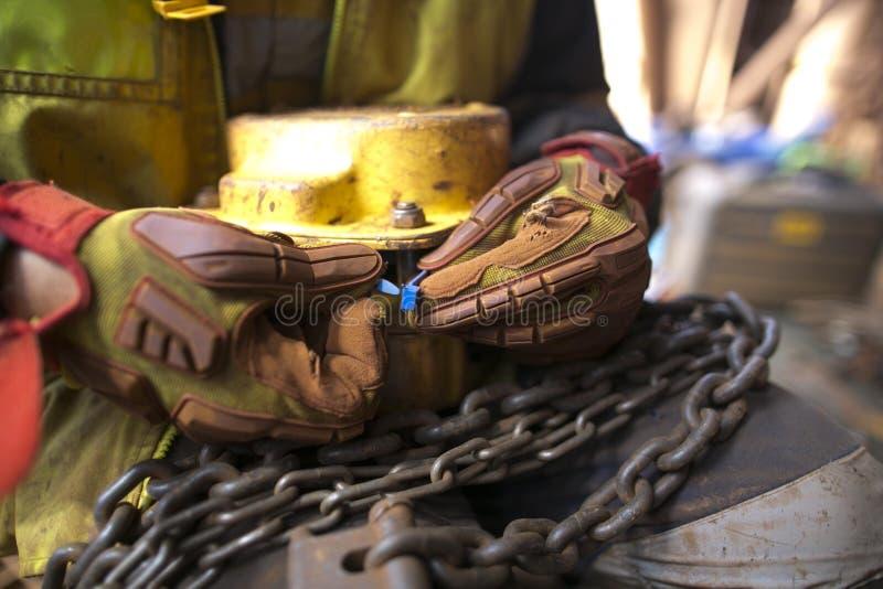 Rigger, der einen Handschuh kontrolliert unter Verwendung des blauen Plastiktags und etikettiert ein der Ton-Kettenhebemaschine d stockfoto