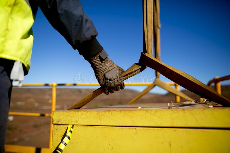 Rigger hand construction worker wearing heavy duty glove holding control a two tones yellow lifting sling royalty free stock photography