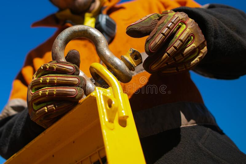 Rigger high risk worker wearing safety heavy duty glove, fastening tensioning pin into D- shape shackle royalty free stock image