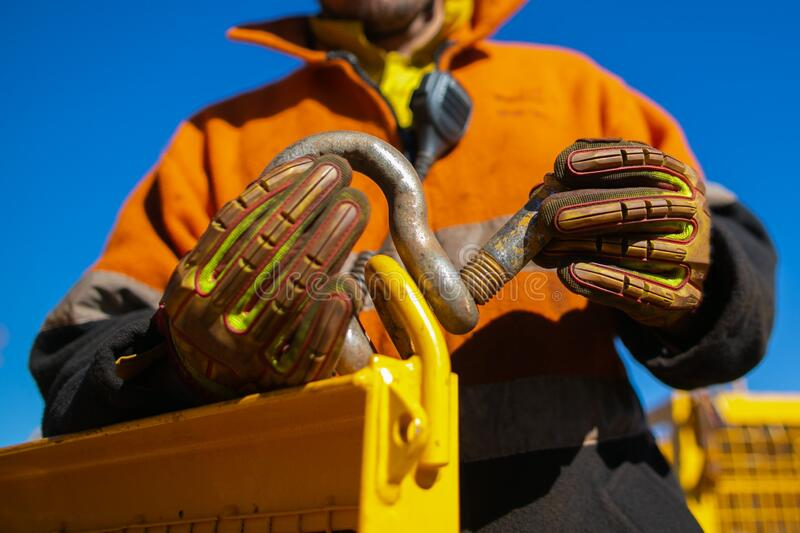 Rigger high risk worker wearing safety heavy duty glove, inserting pin into D- shape shackle stock image