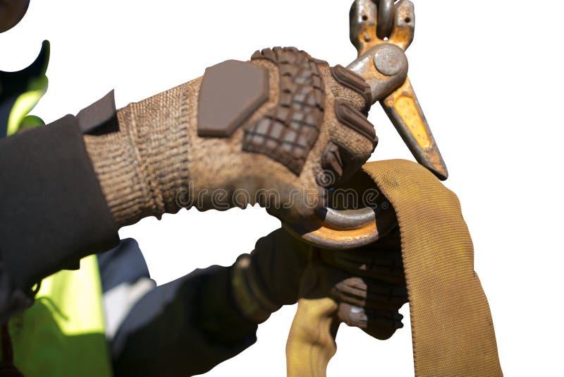 Rigger zeer riskante arbeider die op zwaar werk berekende handschoen dragen en een kraanhaak binnen knippen in gele drie tonen op royalty-vrije stock afbeelding