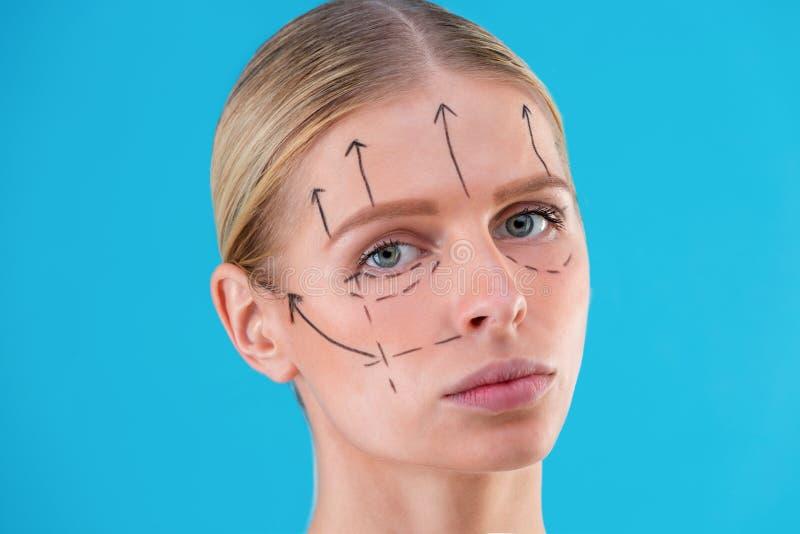 Righe di correzione di tiraggio del Beautician sul fronte della donna Prima del operetion della chirurgia plastica Isolato sul bl fotografia stock