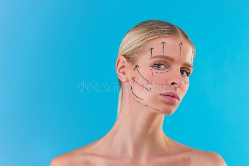 Righe di correzione di tiraggio del Beautician sul fronte della donna Prima del operetion della chirurgia plastica Isolato sul bl fotografia stock libera da diritti