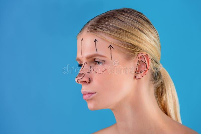Righe di correzione di tiraggio del Beautician sul fronte della donna Prima del operetion della chirurgia plastica Isolato sul bl fotografie stock