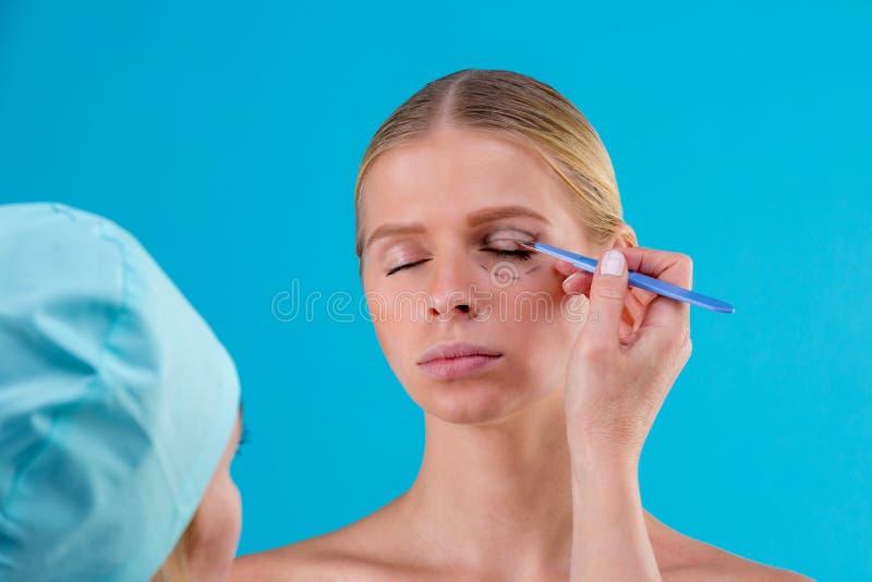Righe di correzione di tiraggio del Beautician sul fronte della donna Prima del operetion della chirurgia plastica Isolato sul bl immagini stock
