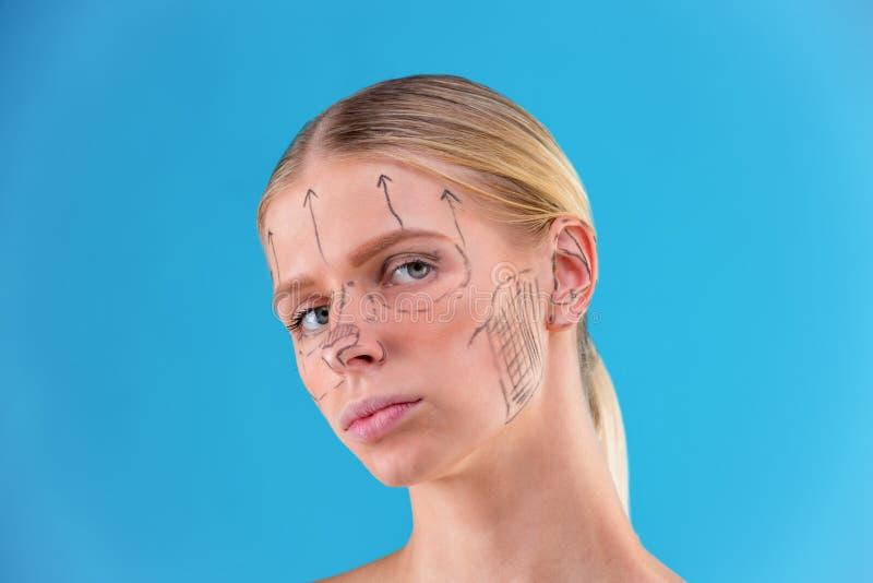 Righe di correzione di tiraggio del Beautician sul fronte della donna Prima del operetion della chirurgia plastica Isolato sul bl immagini stock libere da diritti