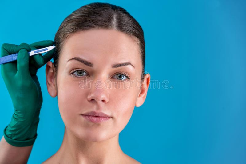 Righe di correzione di tiraggio del Beautician sul fronte della donna Prima del operetion della chirurgia plastica Isolato sul bl immagine stock libera da diritti