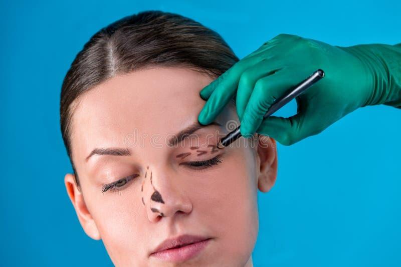 Righe di correzione di tiraggio del Beautician sul fronte della donna Prima del operetion della chirurgia plastica Isolato sul bl fotografie stock libere da diritti