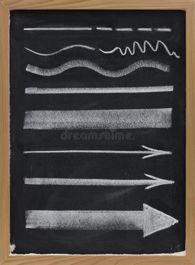 Righe e frecce - gesso bianco sulla lavagna fotografia stock