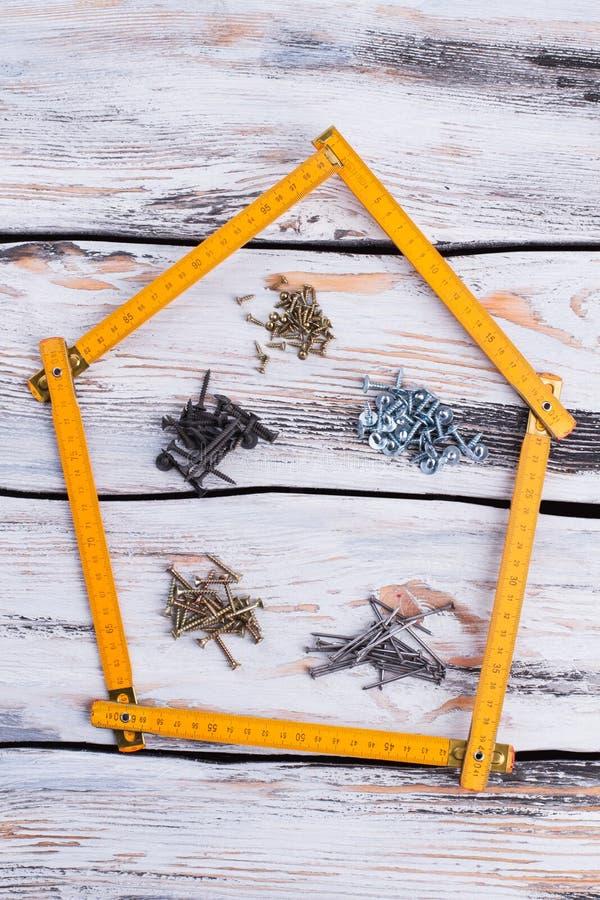 Righello di piegatura in una forma della casa su fondo di legno fotografia stock