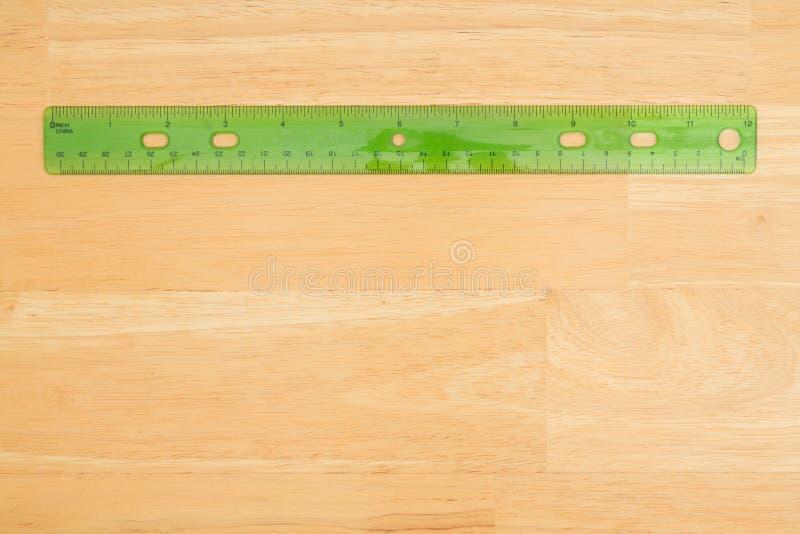 Righello di plastica su un fondo di legno dello scrittorio immagini stock libere da diritti