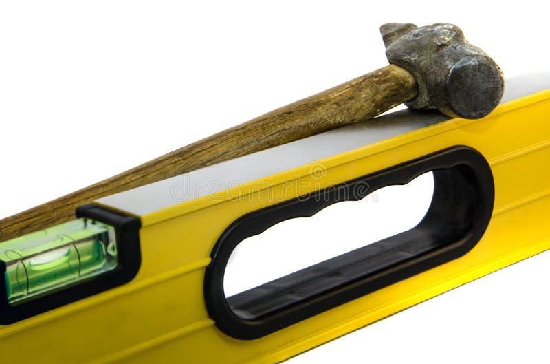 Righello giallo della costruzione con un martello su un fondo bianco fotografia stock