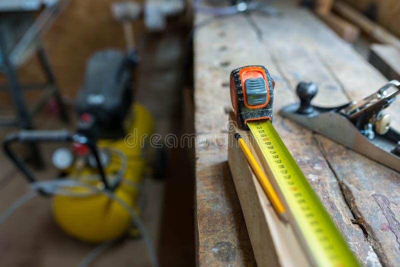 Righello giallo, matita sul bordo di legno di pino, vecchio banco da lavoro incrinato della quercia fotografia stock libera da diritti