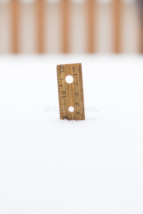 Righello nella neve che misura quanto profondo è fotografie stock