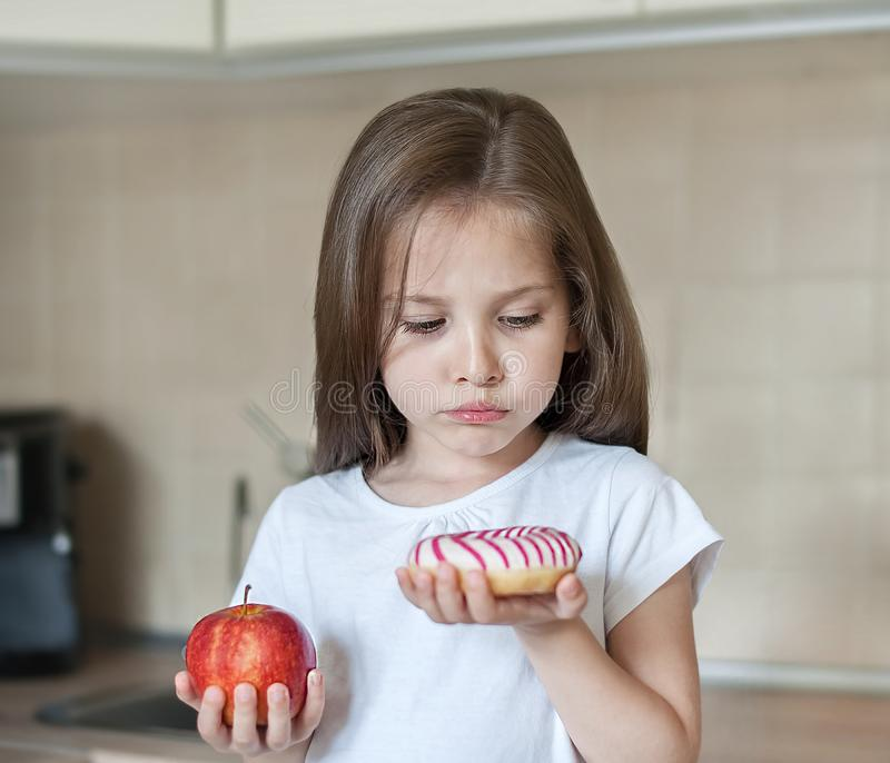 Right choice. Little sad girl holding in hands apple and high-calorie donut. Unhappy child in the kitchen. Dieting, eating stock images