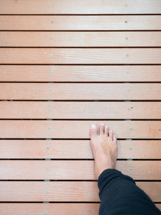 Right foot walking on wooden board path stock photos