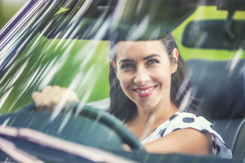 Right-hand driving female sits behind the steering wheel of a car, smiling into the camera through front window stock photos