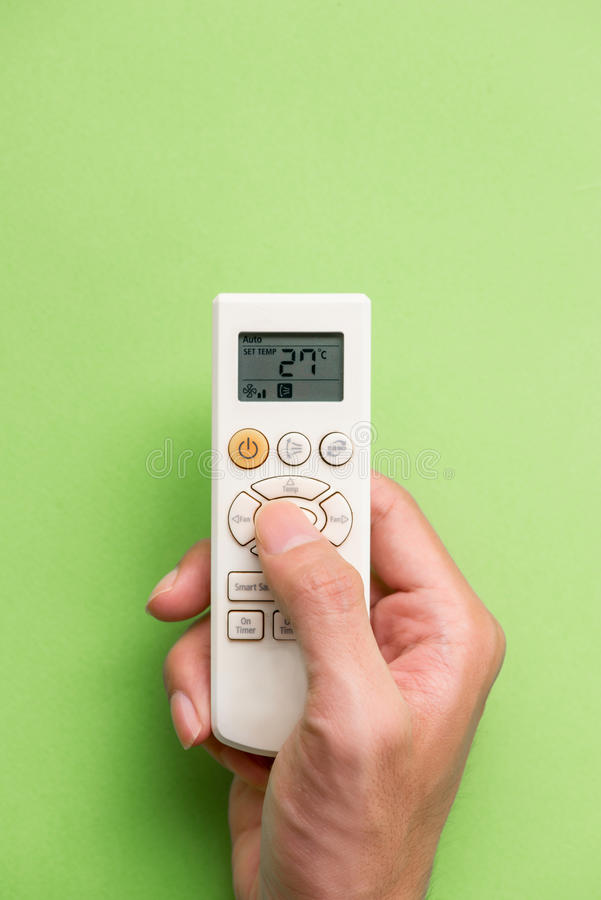 Right hand holding remote air conditioner turn up to 27 celcius. With air conditioner stock image