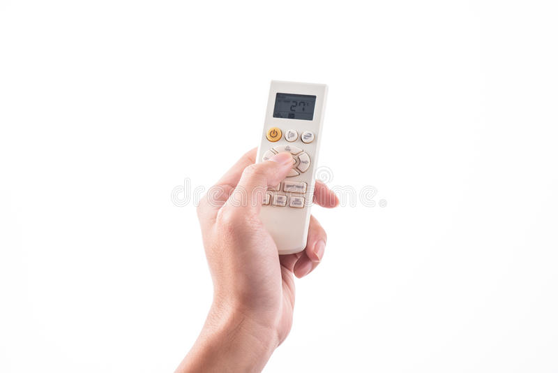Right hand holding remote air conditioner turn up to 27 celcius. With air conditioner royalty free stock photo