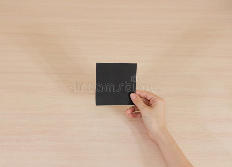 Right hand holding square black paper in the right hand. Leaflet stock photos