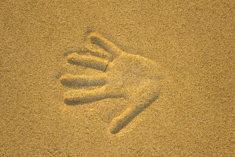 Right hand print in yellow sand close up royalty free stock image