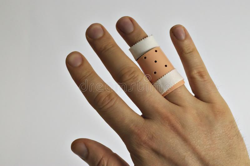 Right hand with a splint on the ring finger. Hurt, closeup, fractured, adult, healthcare, caucasian, health-care, background, sprain, broken, bone, pain stock images