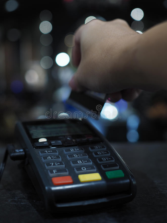 Right hand swiping credit card on black reader payment machine. Right hand with arm holding, swiping credit card magnetic stripe on black moder reader payment stock photography