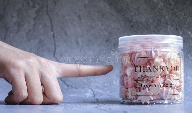 Right Person's Index Finger Pointing Clear Plastic Container Filled on Gray Surface royalty free stock image