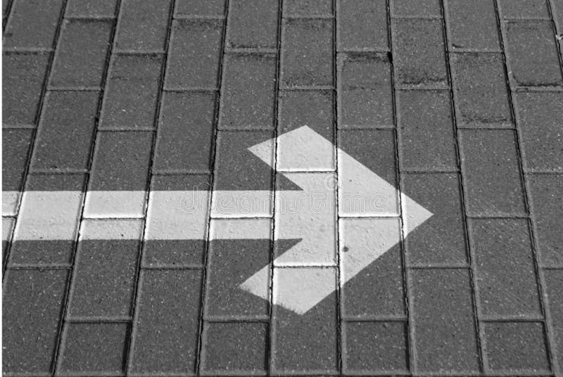 Right pointing arrow on asphalt in black and white. Signs and symbols, grey, gray, direction, traffic, background, road, way, line, street, turn, icon, travel stock photo