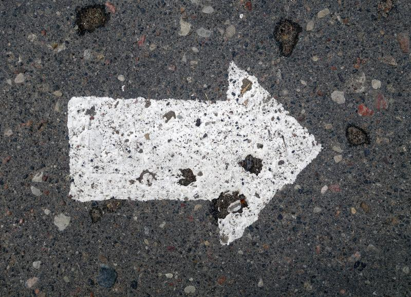 Right pointing arrow on asphalt. Signs and symbols, grey, gray, white, direction, traffic, background, road, way, line, street, turn, black, icon, travel stock photography