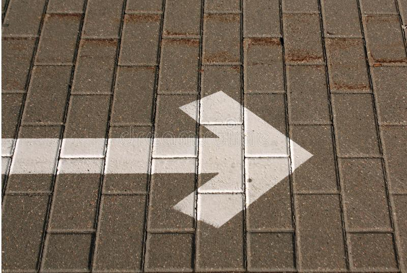 Right pointing arrow on asphalt. Signs and symbols, grey, gray, white, direction, traffic, background, road, way, line, street, turn, black, icon, travel royalty free stock image