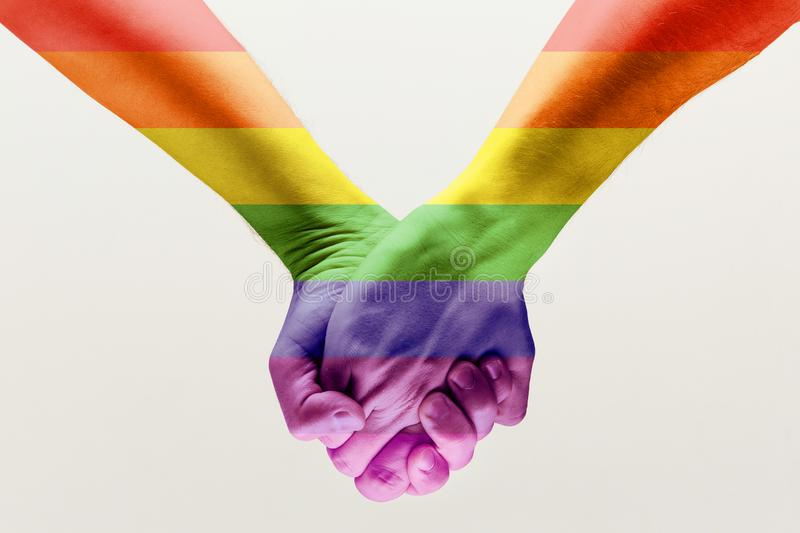 loseup of a gay couple holding hands, patterned as the rainbow flag stock photography
