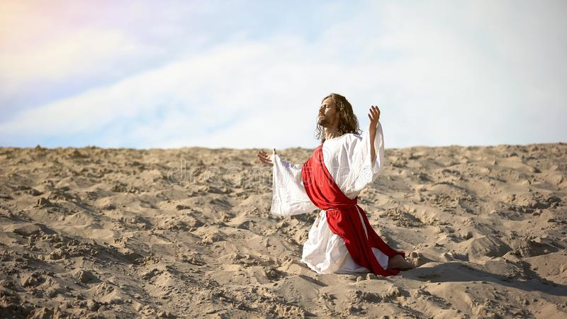Righteous man kneeling in desert, praying to god with raised hands, confession. Stock photo stock images