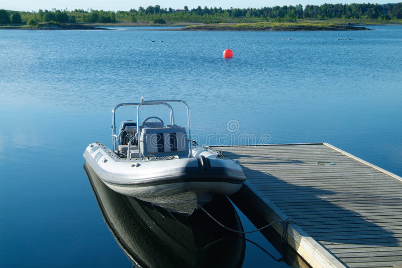 Rigid inflatable boat at a pier stock photos