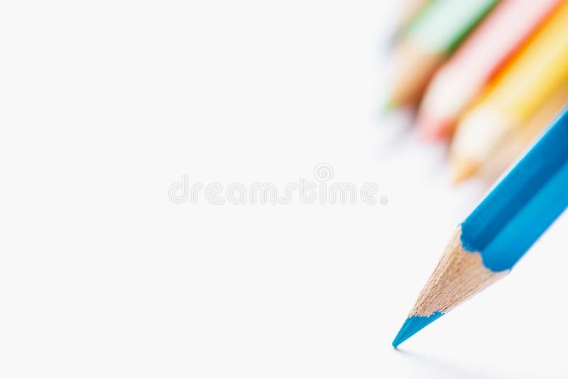 Rij die van Multicolored Potloden in Enig Blauw Scherp Potlood Als achtergrond met Uiteinde aan Leeg Witboek richten Begin van Te stock afbeeldingen