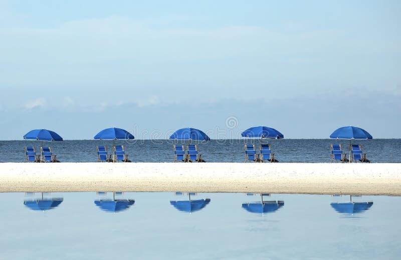 Rij van blauwe strandparaplu's en stoelen royalty-vrije stock foto's